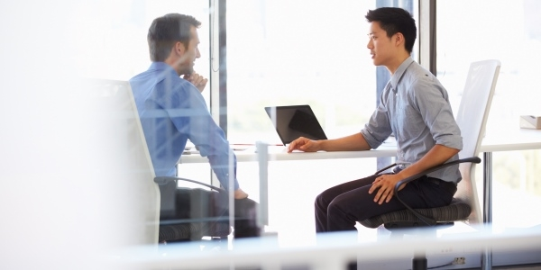 Das Bild zeigt zwei Männer in einem modernen Büro.