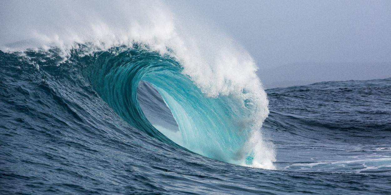 Das Bild zeigt eine Welle im Meer.