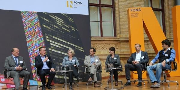 Das Bild zeigt ein Expertenpodium auf dem FONA-Forum.