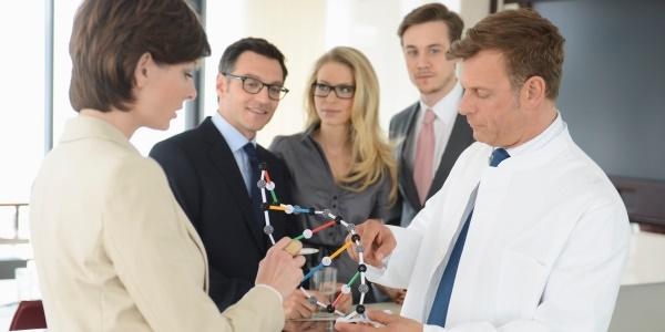 Das Bild zeigt fünf Kollegen, die sich das Modell einer DNA anschauen.