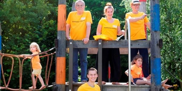 Das Bild zeigt vier Erwachsene und zwei Kinder auf einem Klettergerüst.