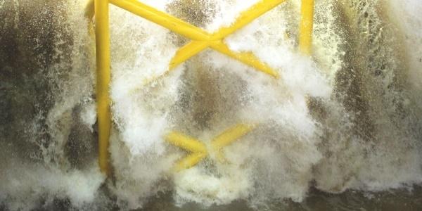 Das Bild zeigt eine brechende Welle auf einer Jacket-Struktur.