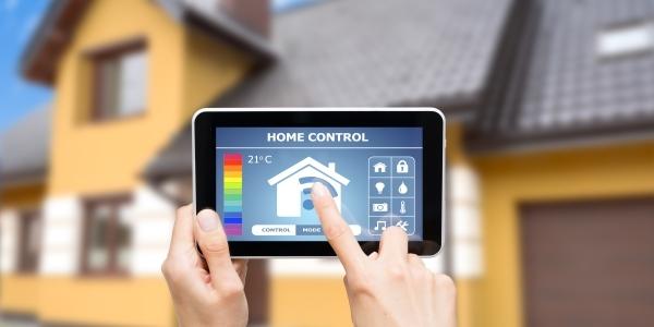 Das Bild zeigt ein Haus im Hintergrund und ein Tablet mit Hausautomationssystem im Vordergrund.