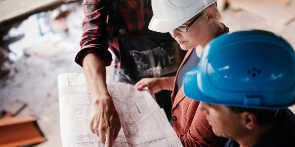 Das Bild zeigt drei Menschen bei der Planung auf einer Baustelle.