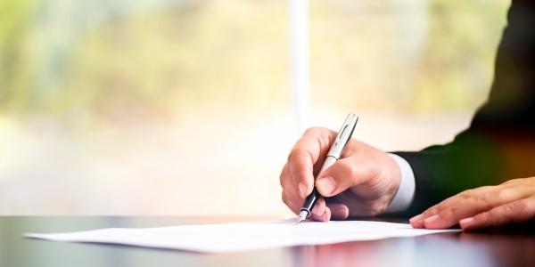 Das Bild zeigt, wie eine Person ein Schriftstück unterschreibt.