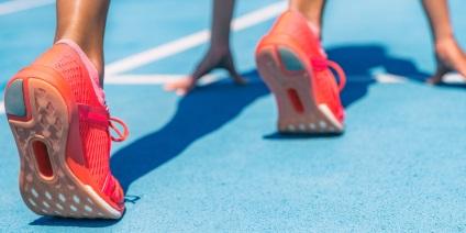 Das Bild zeigt die Füße einer Läuferin in der Startposition.