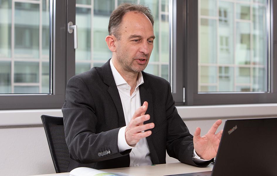 Das Foto zeigt Herrn Dr. Dirk Bessau. Er sitzt an einem Tisch und gestikuliert, vor ihm ist ein Laptop zu sehen. Hinter ihm ist eine Fensterfront