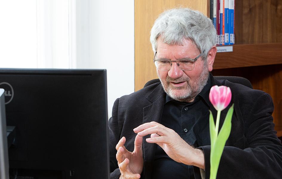 Das Foto zeigt Herrn Prof. Dr. Robert Schlögl. Er sitzt vor einem Computer-Bildschirm und gestikuliert. Im Hintergrund ist ein Bücherregal zu sehen, im Vordergrund steht eine rosa Tulpe auf seinem Schreibtisch.