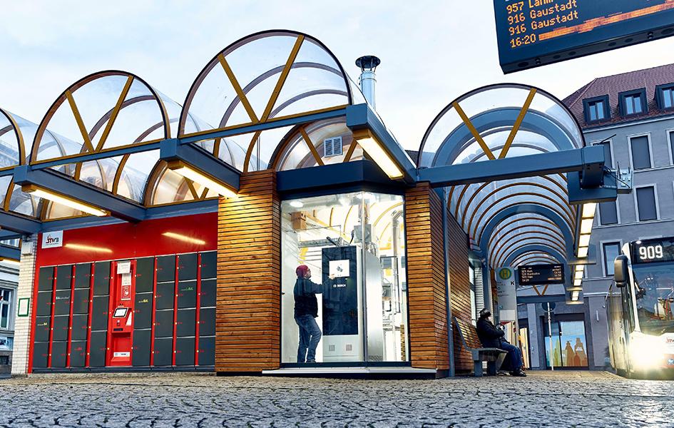 Das Foto zeigt den Zentralen Omnibus Bahnhof in Bamberg. Hier steht eine von 30 Pilotanlagen der Robert Bosch GmbH. Zu sehen ist ein überdachter Ausschnitt des Zentralen Omnibus Bahnhofs. Ein stationäre Brennstoffzelle der Forma Bosch befindet sich in einem Gebäude.