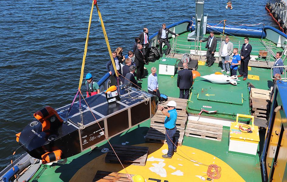 Das Foto zeigt, wie auf einem Schiffsdeck ein Modell eines MUM-Demonstrators an einem Seil ins Wasser gelassen wird. Auf dem Deck befinden sich mehrere Menschen.