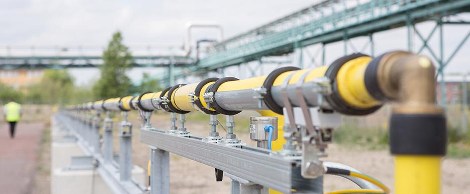 Auf einem großen Gelände ist eine gelbe Rohrleitung an mehreren metallenen Aufnahmen befestigt.