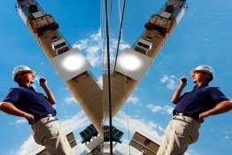 Das Bild zeigt einen Mann mit Helm vor einem Solarturm.