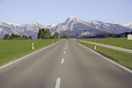 Das Bild zeigt eine Straße und im Hintergrund Berge.