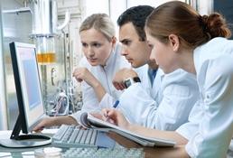 Das Bild zeigt drei Forscherinnen und Forscher an einem Arbeitsplatz im Labor.