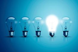 Das Bild zeigt fünf Glühbirnen, eine von ihnen leuchtet.