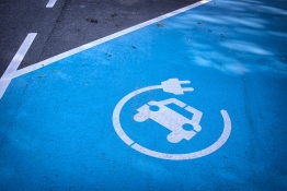 The image shows a parking area with a charging station for electric cars being marked.