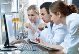 The image shows three researchers working in the laboratory.