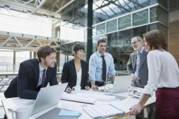 Das Bild zeigt fünf Personen in einer Meeting-Situation.