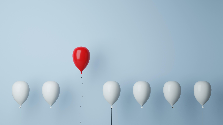 Ein roter Luftballon hebt sich von einer Reihe weißer Luftballons ab und steigt empor.